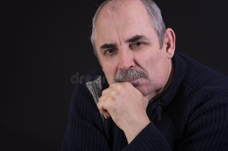 Portret van de rijpe Kaukasische mens die in duisternis denken stock foto's