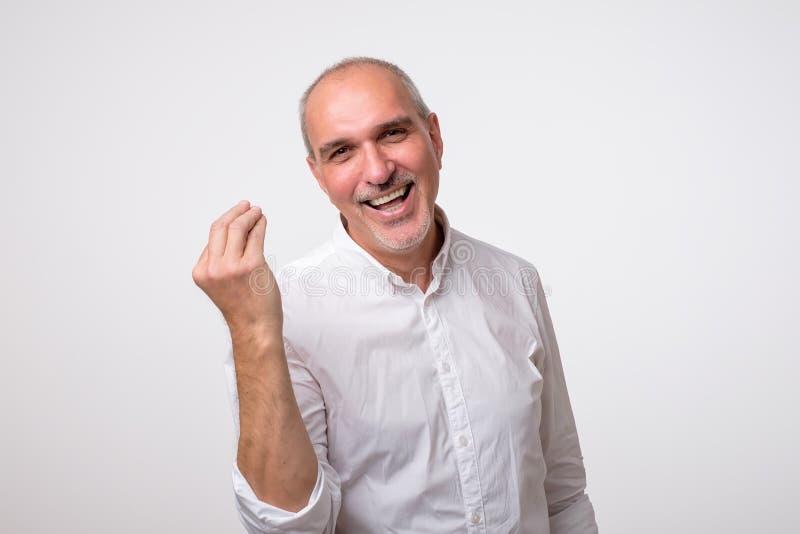 Portret van de rijpe knappe mens in wit overhemd die Italiaans gebaar tonen royalty-vrije stock afbeelding