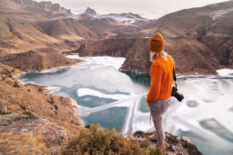 Portret van de rug van de fotograaf van de meisjesreiziger in een oranje sweater en hoed met een camera in hand in royalty-vrije stock afbeeldingen