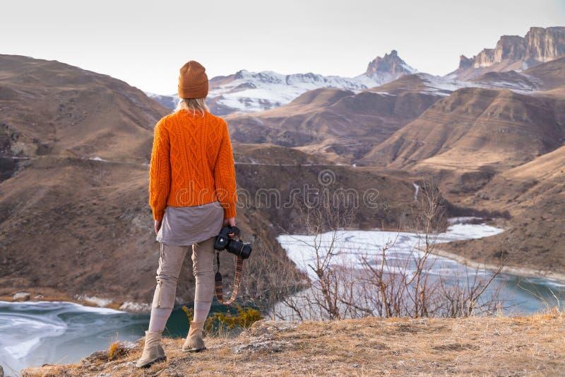 Portret van de rug van de fotograaf van de meisjesreiziger in een oranje sweater en hoed met een camera in hand in stock afbeelding