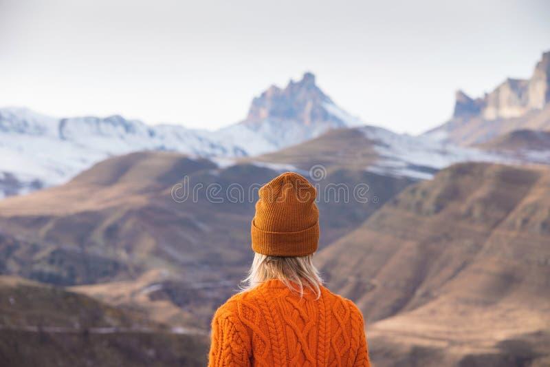 Portret van de rug van de meisjesreiziger in een oranje sweater en hoed in de bergen tegen de achtergrond van a stock foto's