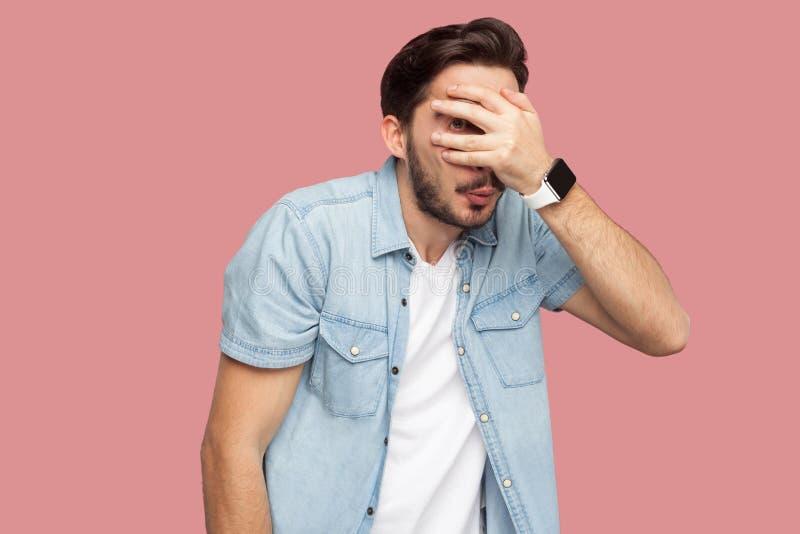 Portret van de schuwe, doen schrikken of glurende gebaarde jonge mens in blauw toevallig stijloverhemd die behandelend zijn ogen  royalty-vrije stock foto's