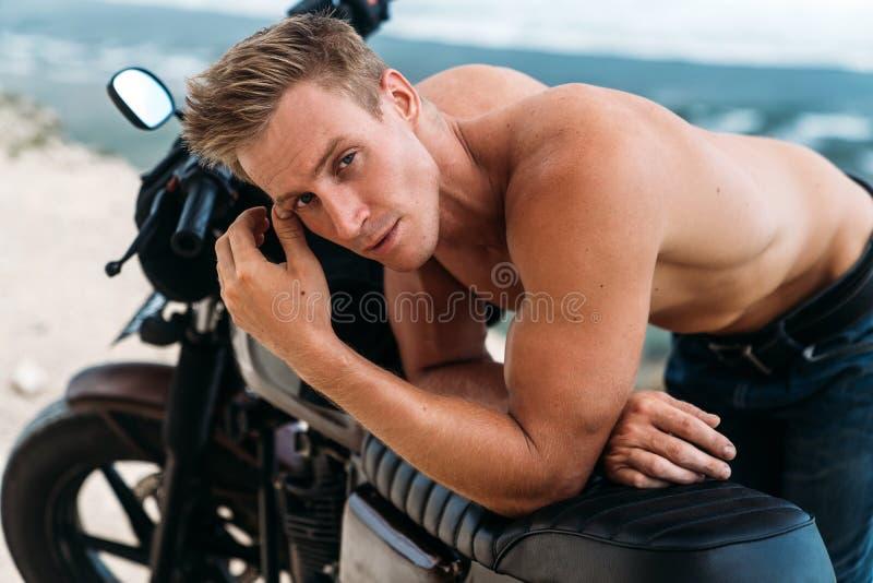 Portret van de sexy atletische mens met naakt torso op douanemotor met oceaan bij achtergrond royalty-vrije stock foto