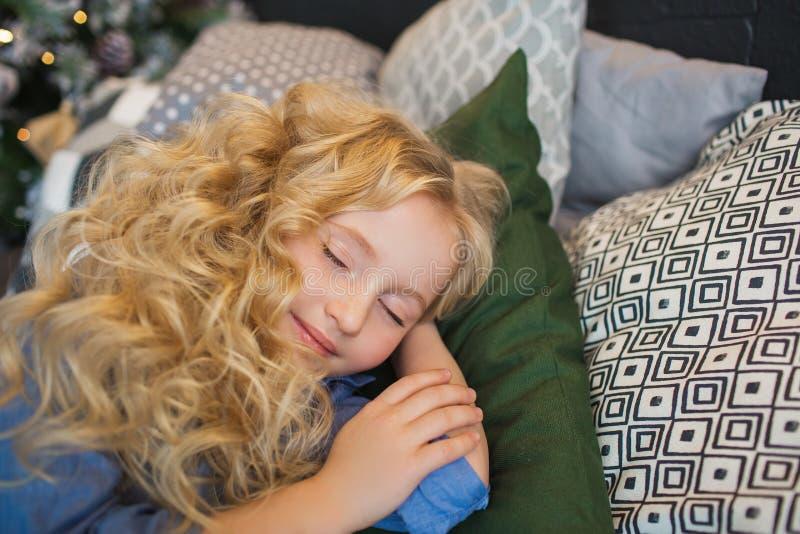 Portret van de slaap van het blondemeisje op hoofdkussens op een bed in Kerstmistijd stock foto's