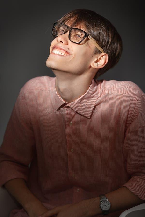 Portret van de sluwe grappige jonge Kaukasische mens die glazen, overhemd in een strook dragen die binnen met gelukkig gezicht si stock afbeelding