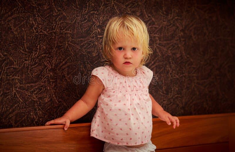 portret van de status van weinig blondemeisje in roze tegen bruine muur stock fotografie