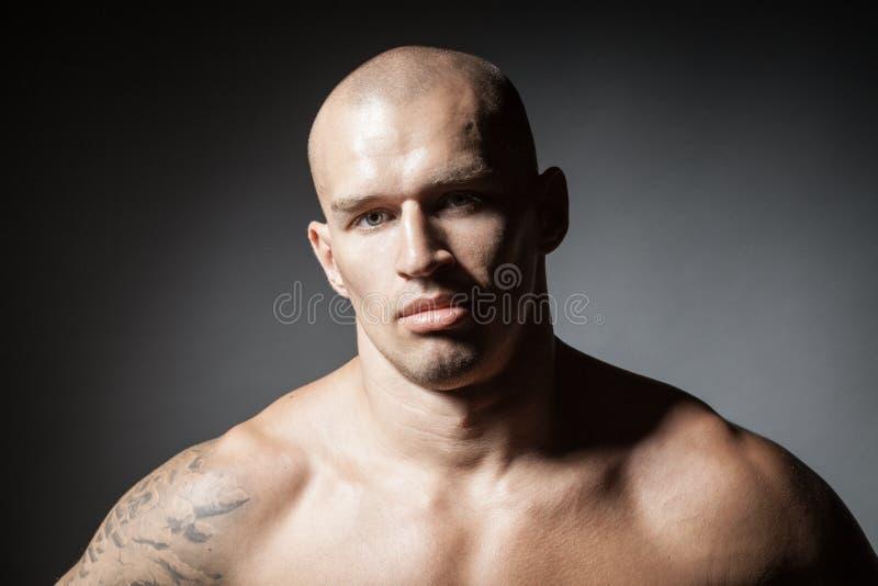 Portret van de sterke die mens op dark wordt geïsoleerd royalty-vrije stock afbeelding