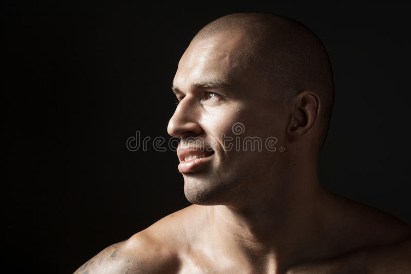 Portret van de sterke glimlachende die mens op zwarte achtergrond wordt geïsoleerd royalty-vrije stock foto