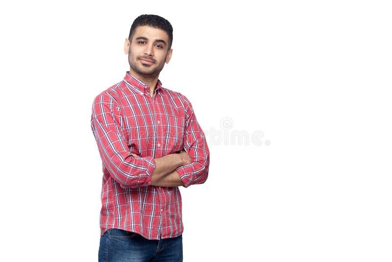 Portret van de succesvolle trotse tevreden knappe gebaarde jonge mens in rood geruit overhemd die en zich camera bevinden bekijke stock afbeeldingen
