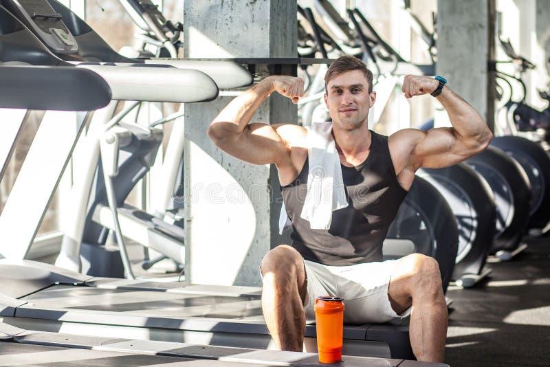 Portret van de succesvolle zitting van de atleten knappe mannelijke mens tijdens tredmolenoefening in gymnastiek, vermoeid sportm stock foto's