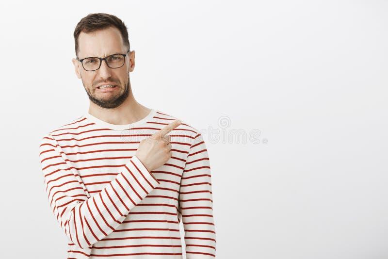 Portret van de teleurgestelde grappige Kaukasische mens die antipathie tonen terwijl het richten op hogere juiste hoek die, worde stock afbeelding
