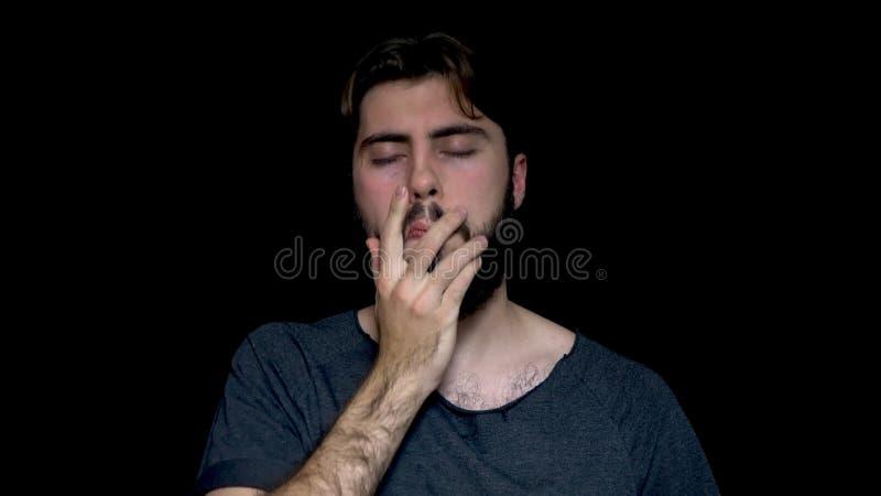 Portret van de teleurgestelde, verstoorde mens met baard die zijn die gezicht met palm behandelt, op zwarte achtergrond wordt geï royalty-vrije stock foto's