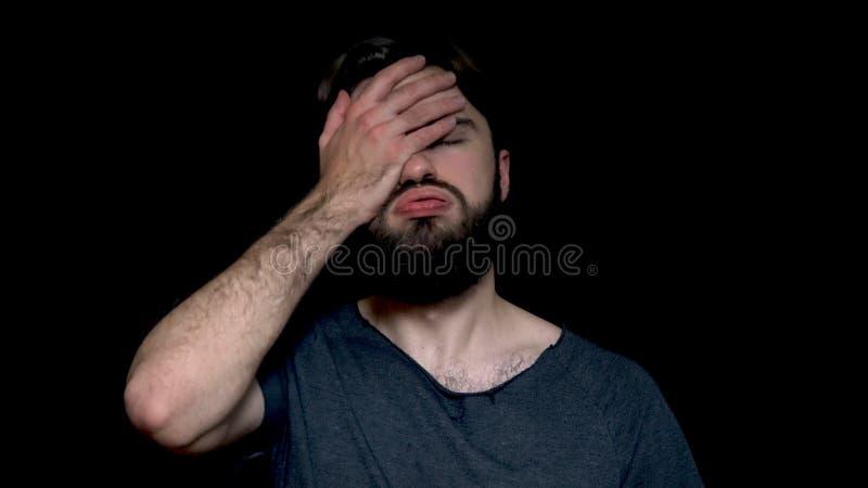 Portret van de teleurgestelde, verstoorde mens met baard die zijn die gezicht met palm behandelt, op zwarte achtergrond wordt geï stock foto