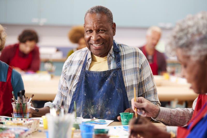 Portret van de Teruggetrokken Hogere Mens die Art Class In Community Centre bijwonen stock foto's
