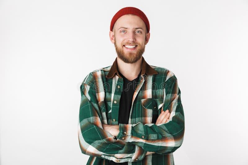 Portret van de tevreden mens die hoed en plaidoverhemd draagt dat met gekruiste wapens glimlacht, terwijl status geïsoleerd over  royalty-vrije stock foto's