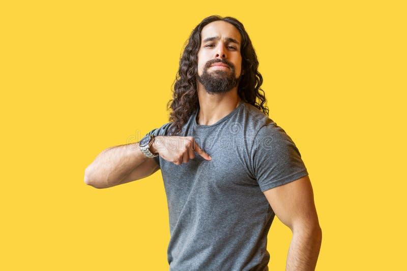 Portret van de trotse gebaarde jonge mens met lang krullend haar in grijze t-shirt die, richten en camera bekijken met bevinden z stock foto