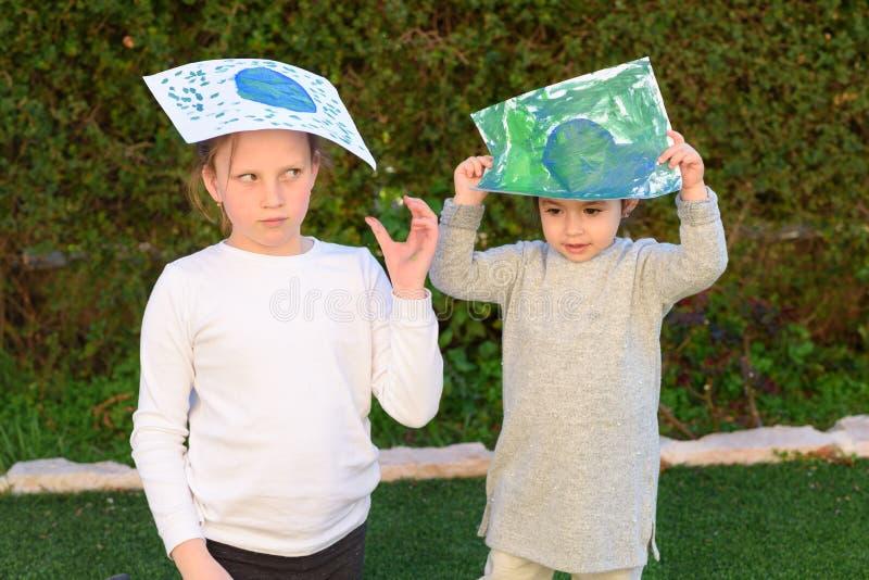 Portret van de twee leuke meisjes die de bol van de tekeningsaarde houden Jonge geitjes paintig beeld van aarde die pret hebben o stock foto