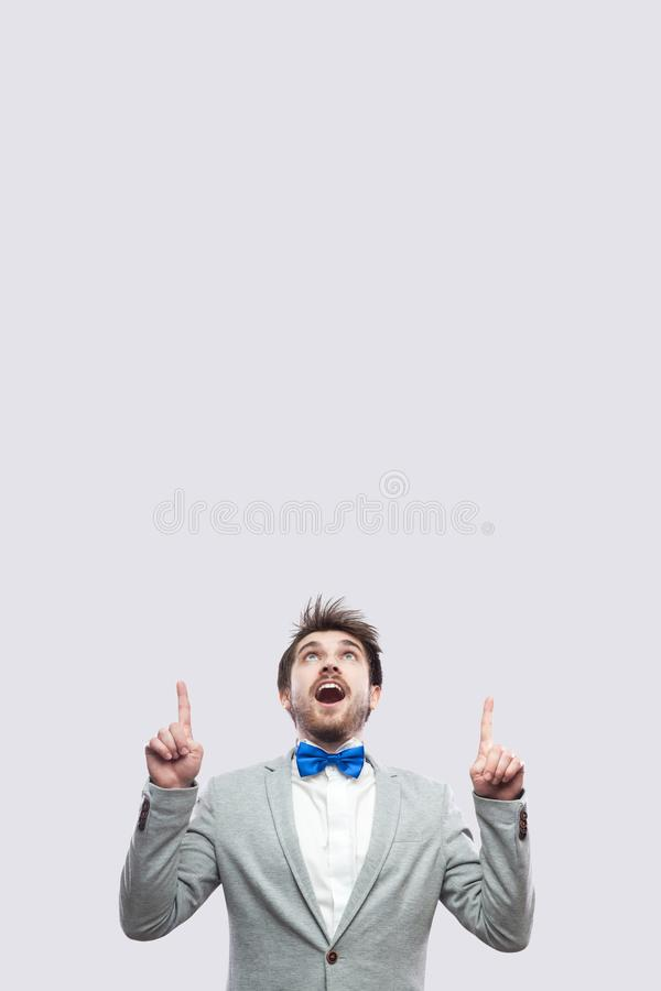 Portret van de verbaasde knappe gebaarde mens in toevallig grijs kostuum en blauwe vlinderdas status bekijkend en richtend op omh royalty-vrije stock foto
