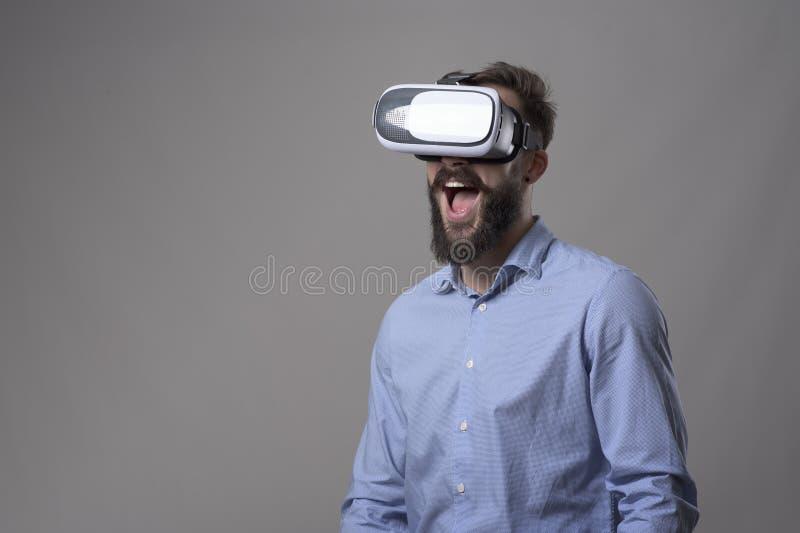 Portret van de verbaasde opgewekte jonge gebaarde mens die op virtuele werkelijkheidsglazen met open monduitdrukking letten stock afbeelding