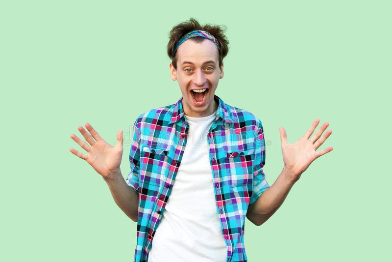 Portret van de verraste gelukkige jonge mens in toevallige blauwe geruite overhemd en hoofdband status, opgeheven wapens en het b royalty-vrije stock afbeeldingen