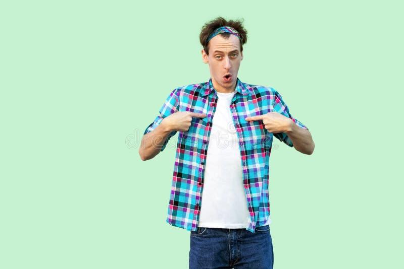 Portret van de verraste jonge mens in toevallig blauw geruit overhemd en hoofdband die, op zich richten en camera bekijken bevind royalty-vrije stock foto