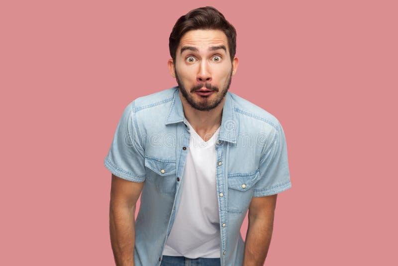 Portret van de verraste knappe gebaarde jonge mens in blauw toevallig stijloverhemd die en zich camera met geschokt bevinden beki royalty-vrije stock foto