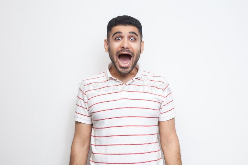 Portret van de verraste knappe gebaarde jonge mens in gestreepte t-shirt die zich met open mond bevinden en camera met verbaasd b stock fotografie