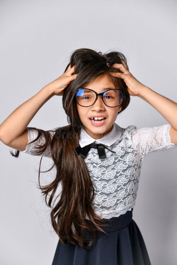 Portret van de verraste opgewekte handen van de tienerholding achter hoofd, open mond met bruin lang die haar over grijze achterg royalty-vrije stock foto