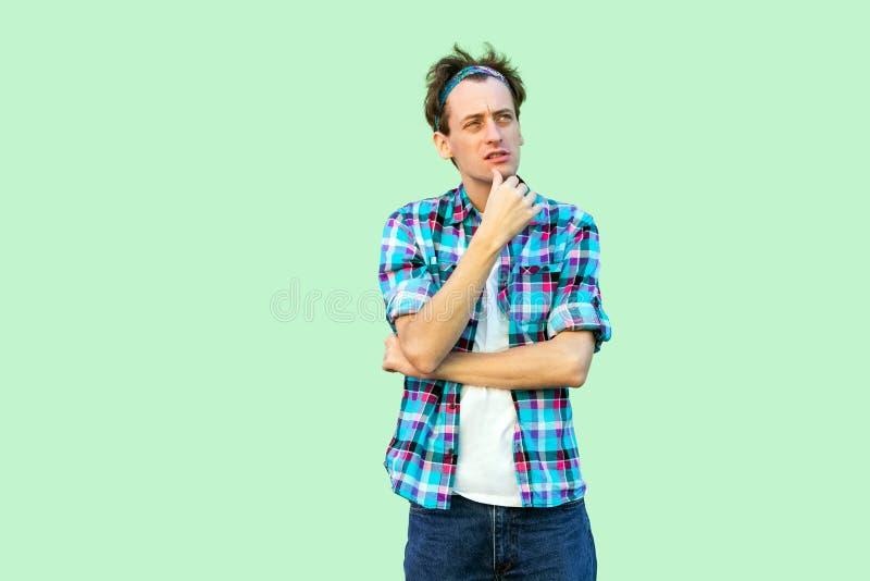 Portret van de verwarde jonge mens in toevallig blauw geruit overhemd en hoofdband die, zich wat betreft kin bevinden, denkend en stock foto