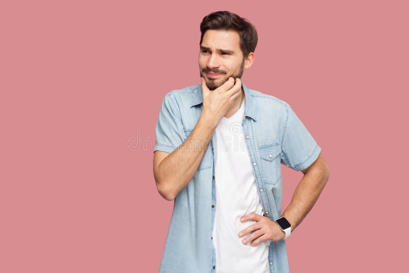 Portret van de verwarde knappe gebaarde jonge mens in blauw toevallig stijloverhemd die krassend baard en denkend wat om te doen  royalty-vrije stock afbeeldingen