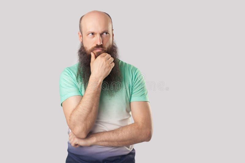 Portret van de verwarde midden oude kale mens met lange baard in lichtgroene zich met hand op kin bevinden en t-shirt die weg eru royalty-vrije stock fotografie