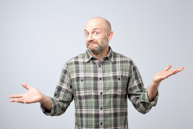 Portret van de verwarde rijpe mens D die zich over het witte gesturing als achtergrond met handen bevinden royalty-vrije stock fotografie