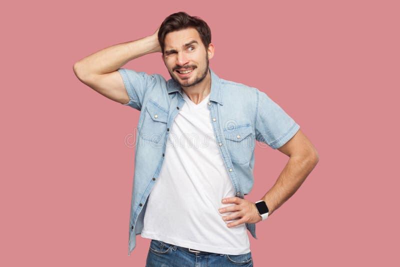 Portret van de vraag knappe gebaarde jonge mens in blauw toevallig stijloverhemd die en zich weg en wat denken om te doen bevinde stock foto