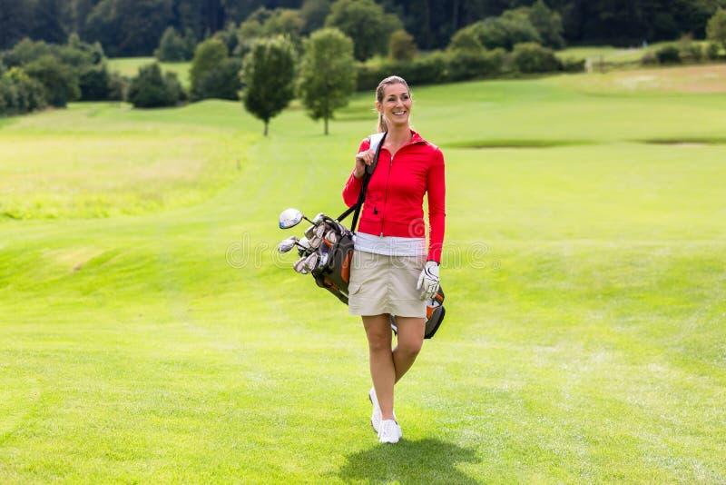 Portret van de vrouwelijke zak van het golfspeler dragende golf stock foto's