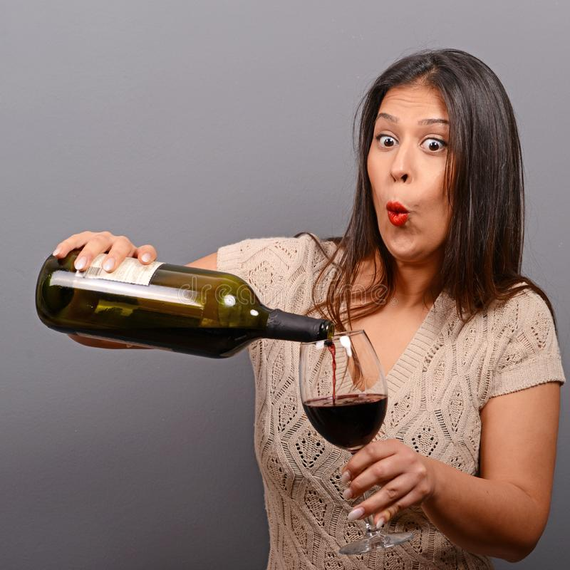 Portret van de wijnfles en glas van de vrouwenholding tegen grijze achtergrond stock foto