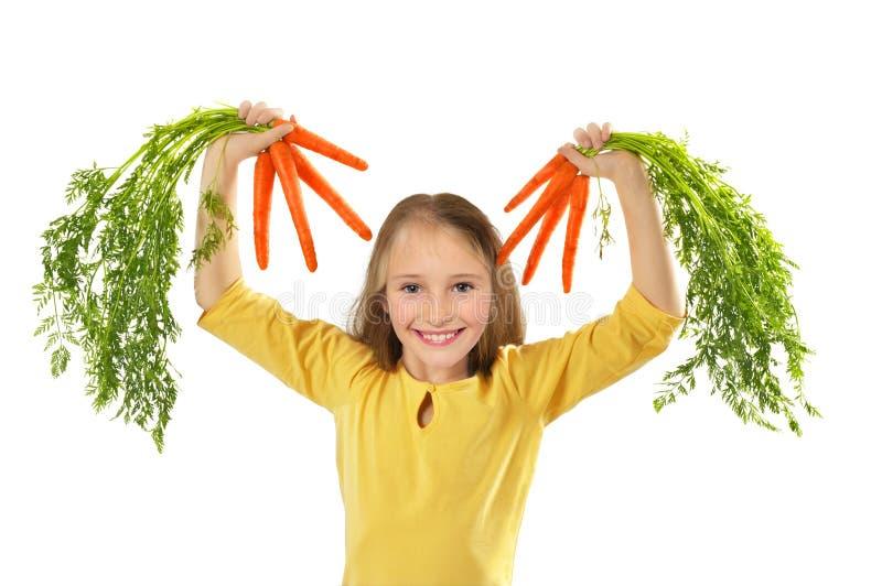 Meisje met wortelen stock foto's