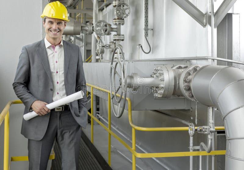 Portret van de zekere jonge mannelijke blauwdruk van de architectenholding door machines in de industrie stock afbeeldingen