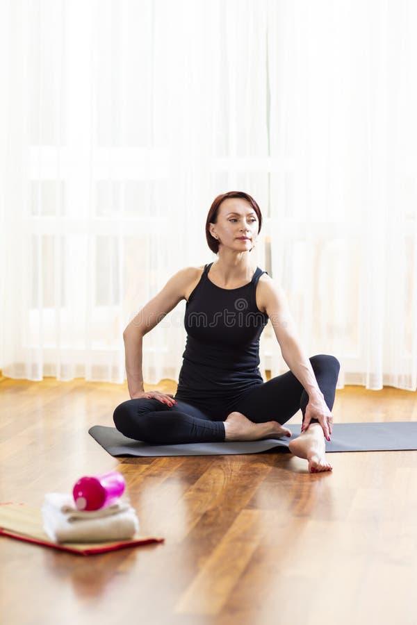 Portret van de Zitting van de Yogavrouw op Sportmat binnen met Sporttoebehoren in Voorgrond royalty-vrije stock fotografie