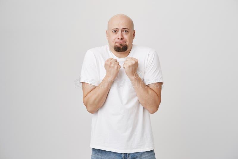 Portret van doen schrikken of bang gemaakt kaal Europees mannetje met baard clasping vuisten dichtbij borst en status over grijs stock fotografie