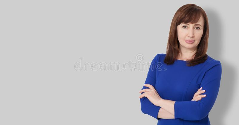 Portret van donkerbruine ernstige middenleeftijds chef- vrouw in bedrijfsdiekleding op grijze achtergrond wordt geïsoleerd Gekrui royalty-vrije stock afbeelding