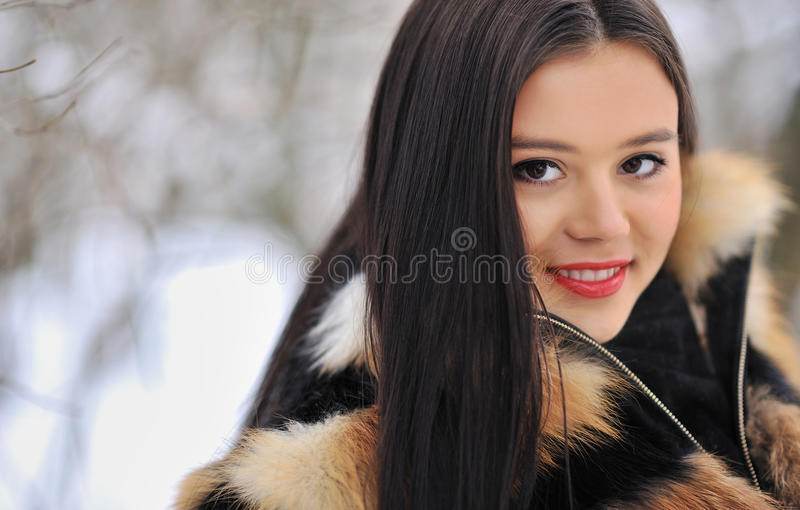 Portret van donkerbruine jonge vrouw in bontjas bij de winter backgroun stock afbeeldingen