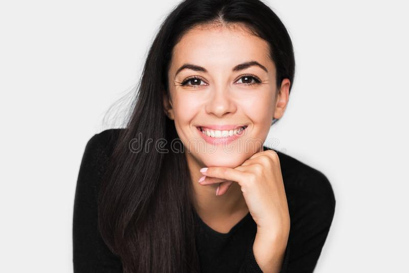 Portret van donkerbruine leuke vrouw met mooie en gezonde toothy glimlach, met hand op kin royalty-vrije stock afbeelding