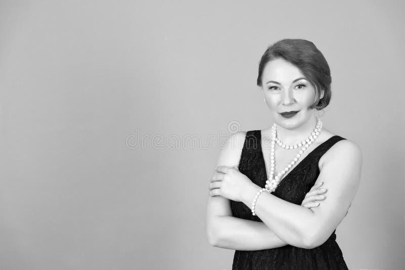 Portret van Donkerbruine vrouw op grijze achtergrond Dame in zwarte dre stock foto