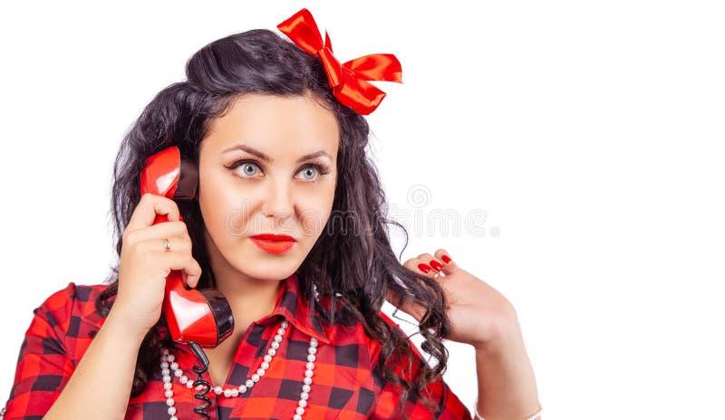 Portret van donkerbruine vrouw in rode kleding met telefoon in pinup stule stock fotografie