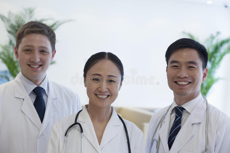 Portret van drie glimlachende artsen in het ziekenhuis, multi-etnische groep royalty-vrije stock afbeeldingen