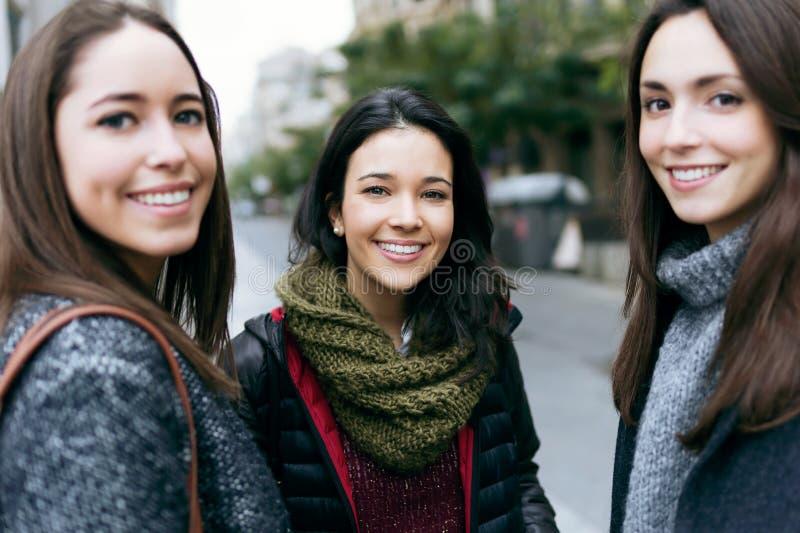 Portret van drie jonge mooie en vrouwen die spreken lachen royalty-vrije stock foto's