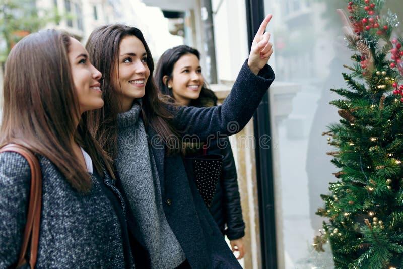 Portret van drie jonge mooie vrouwen die de winkelwind bekijken royalty-vrije stock afbeeldingen