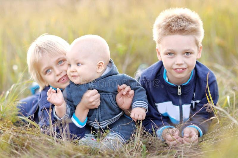 Portret van drie kleine jongens op het strand stock foto's