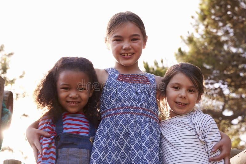 Portret van Drie Meisjes die in openlucht thuis in Tuin spelen stock fotografie