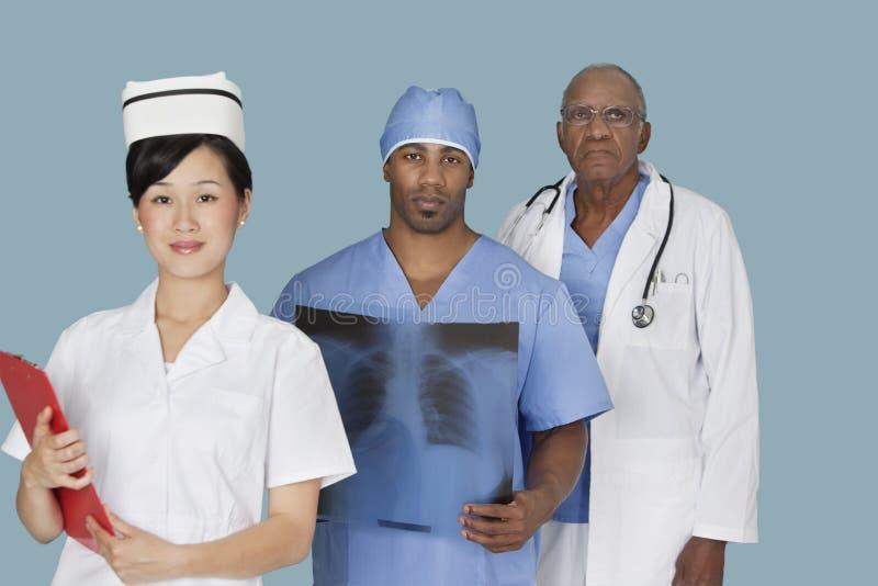 Portret van drie multi etnische medische beroeps over lichtblauwe achtergrond royalty-vrije stock foto's